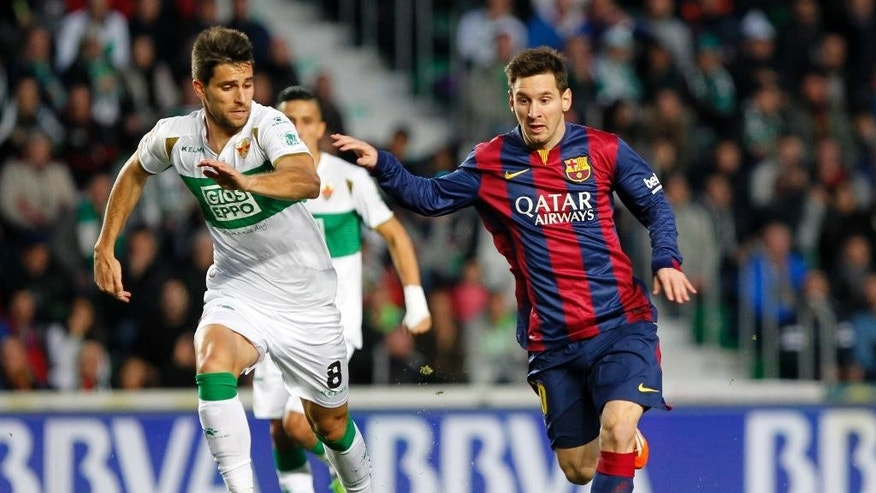 Barcelona's Lionel Messi, from Argentina, right, duels for the ball with Elche's Adrian Gonzalez, left, during a Spanish La Liga soccer match between Elche and Barcelona, at the Martinez Valero stadium in Elche, Spain, Saturday, Jan. 24, 2015. Barcelona won the match 6-0.(AP Photo/Fernando Bustamante)