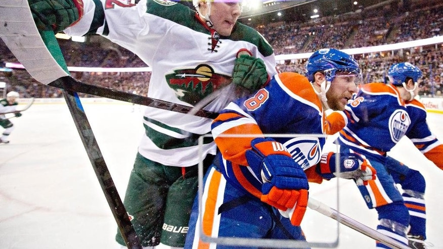 Minnesota Wild's Christian Folin (5) knocks over Edmonton Oilers' Matt Fraser (28) as goalie Devan Dubnyk (40) looks for the puck during the second period of an NHL hockey game Tuesday, Jan. 27, 2015, in Edmonton, Alberta. (AP Photo/The Canadian Press, Jason Franson)