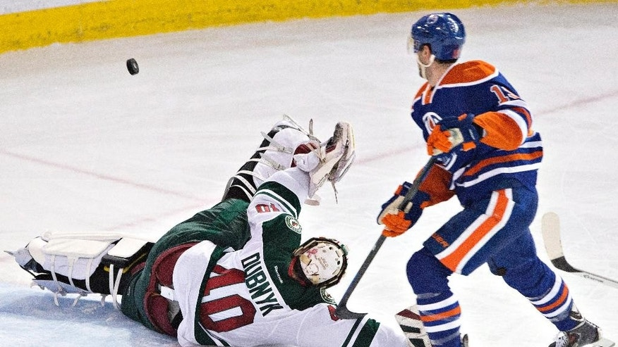 Minnesota Wild goalie Devan Dubnyk (40) makes the save on Edmonton Oilers' Justin Schultz (19) during the second period of an NHL hockey game Tuesday, Jan. 27, 2015, in Edmonton, Alberta. (AP Photo/The Canadian Press, Jason Franson)