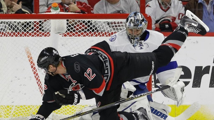 Carolina Hurricanes' Eric Staal (12) falls while attempting to score against Tampa Bay Lightning goalie Ben Bishop during the first period of an NHL hockey game in Raleigh, N.C., Tuesday, Jan. 27, 2015. (AP Photo/Gerry Broome)