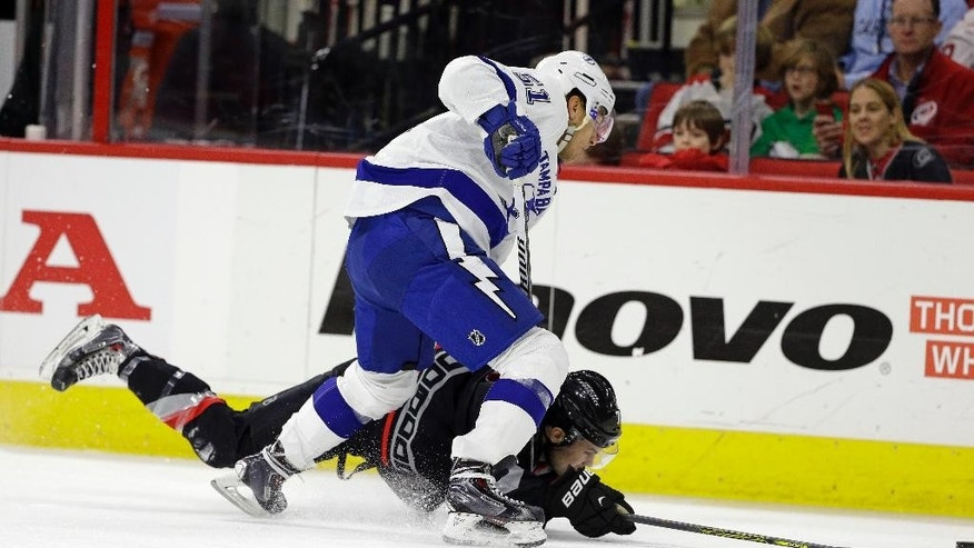 Carolina Hurricanes' Ryan Murphy falls to the ice while chasing the puck with Tampa Bay Lightning's Valtteri Filppula (51), of Finland, during the first period of an NHL hockey game in Raleigh, N.C., Tuesday, Jan. 27, 2015. (AP Photo/Gerry Broome)