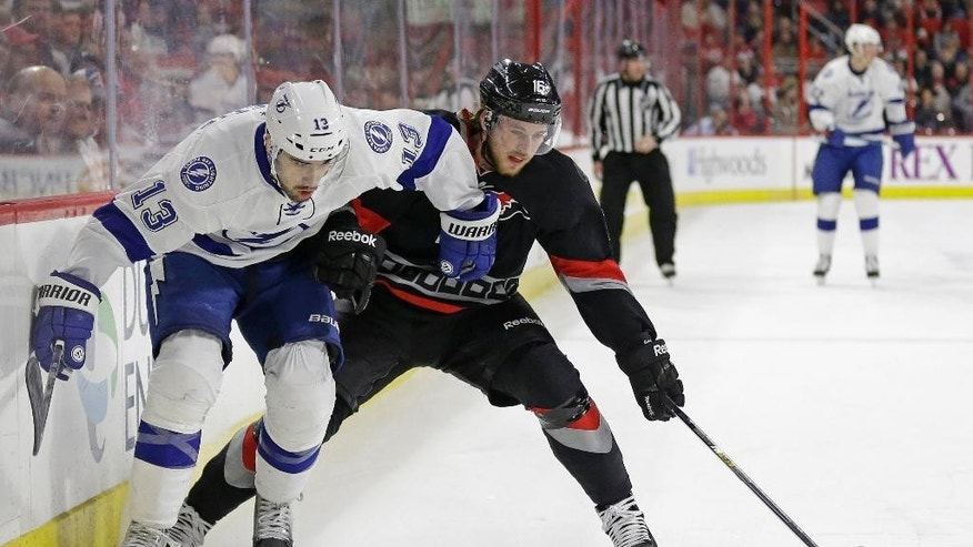 Tampa Bay Lightning's Cedric Paquette (13) and Carolina Hurricanes' Elias Lindholm (16), of Sweden, chase the puck during the first period of an NHL hockey game in Raleigh, N.C., Tuesday, Jan. 27, 2015. (AP Photo/Gerry Broome)