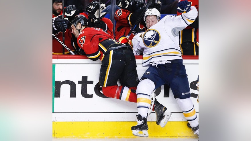 Buffalo Sabres' Nicolas Deslauriers, right, collides along the boards with Calgary Flames' Lance Bouma during the third period of an NHL hockey game Tuesday, Jan. 27, 2015 in Calgary, Alberta. (AP Photo/The Canadian Press, Larry MacDougal)