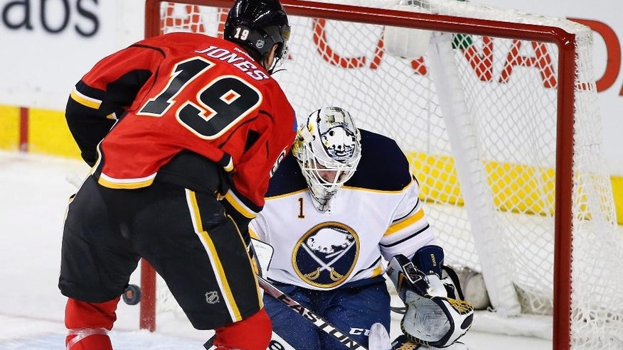 Buffalo Sabres goalie Jhonas Enroth, right, from Sweden, makes a save against Calgary Flames' David Jones during the second period on an NHL hockey game, Tuesday, Jan. 27, 2015 in Calgary, Alberta. (AP Photo/Canadian Press, Larry MacDougal)