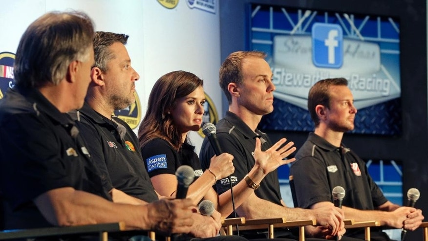 Danica Patrick, center, speaks to the media as Kevin Harvick, second from right, Kurt Busch, right, Tony Stewart, second from left, and team co-owner Gene Haas, left, look on during the NASCAR Charlotte Motor Speedway media tour in Charlotte, N.C., Tuesday, Jan. 27, 2015. (AP Photo/Chuck Burton)