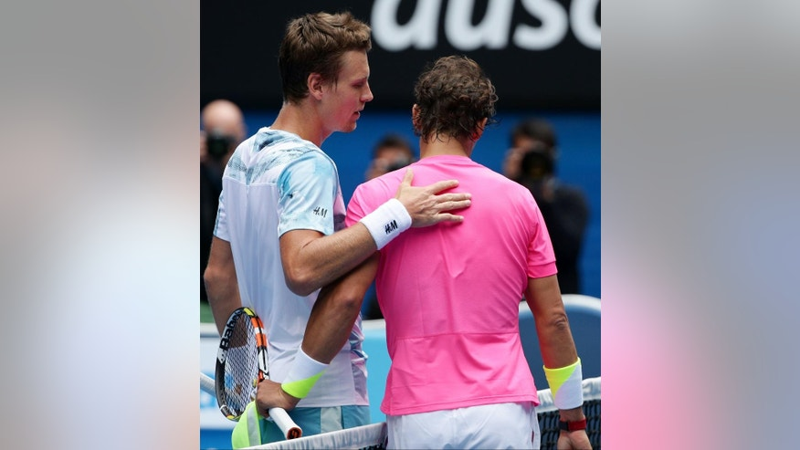 Tomas Berdych of the Czech Republic, left,  talks with Rafael Nadal of Spain at the net after winning their quarterfinal match at the Australian Open tennis championship in Melbourne, Australia, Tuesday, Jan. 27, 2015. (AP Photo/Rob Griffith)