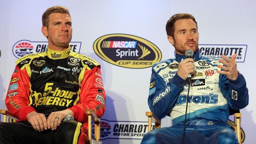 Driver Brian Vickers, right, speaks to the media as teammate Clint Bowyer, left, looks on during the NASCAR Charlotte Motor Speedway media tour in Charlotte, N.C., Tuesday, Jan. 27, 2015. (AP Photo/Chuck Burton)