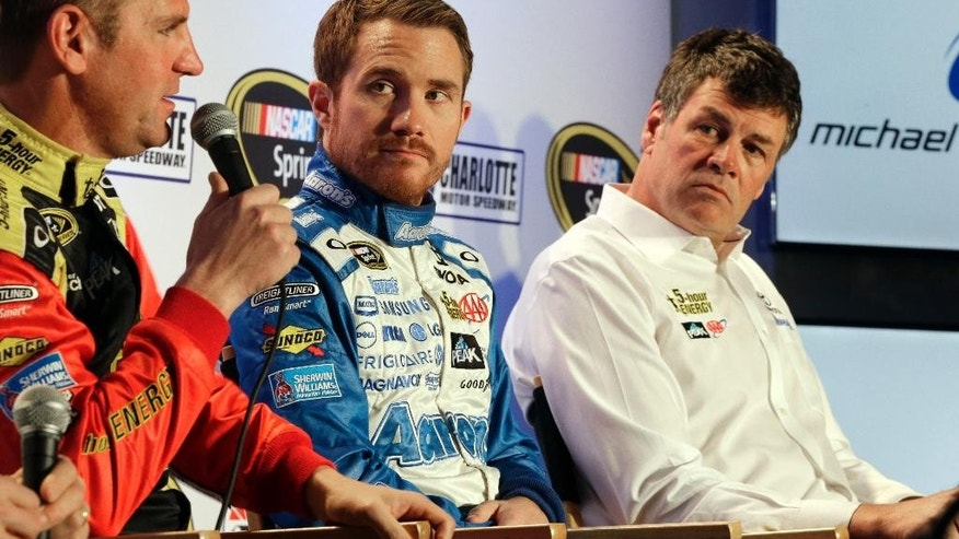 Driver Clint Bowyer, left, speaks to the media as team owner Michael Waltrip, right, and driver Brian Vickers, center, listen during the NASCAR Charlotte Motor Speedway media tour in Charlotte, N.C., Tuesday, Jan. 27, 2015. (AP Photo/Chuck Burton)