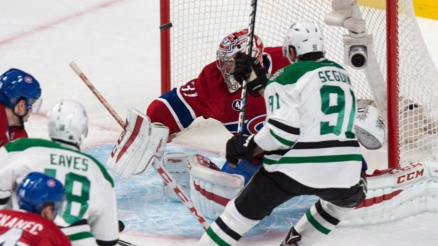 The puck goes off the goal post behind Montreal Canadiens goalie Carey Price on a shot by Dallas Stars' Tyler Seguin during the first period of an NHL hockey game Tuesday, Jan. 27, 2015, in Montreal. (AP Photo/The Canadian Press, Paul Chiasson)