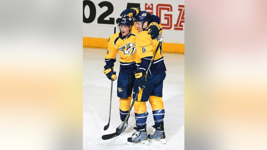 Nashville Predators defenseman Roman Josi (59), of Switzerland, is congratulated by defenseman Shea Weber (6) after scoring a goal during the second period of an NHL hockey game against the Colorado Avalanche on Tuesday, Jan. 27, 2015, in Nashville, Tenn. (AP Photo/Mark Zaleski)
