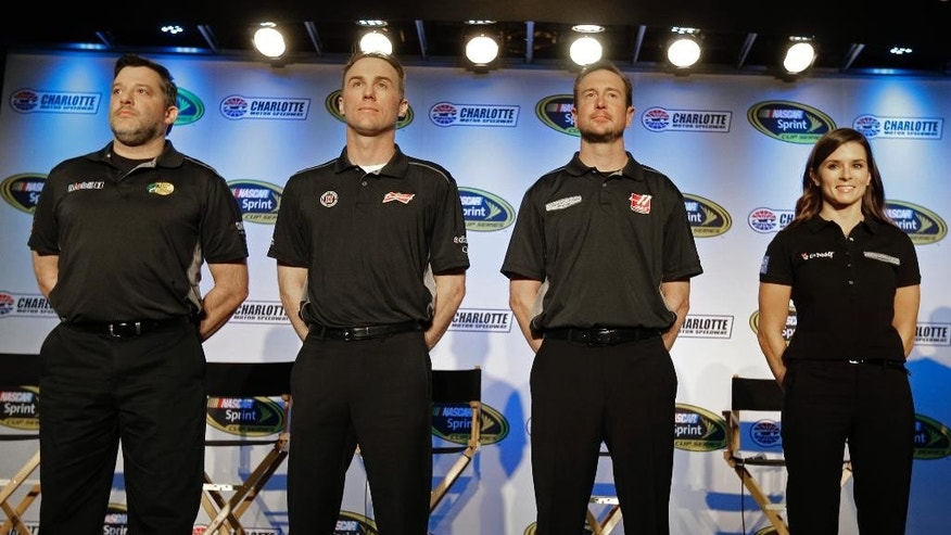 Stewart-Haas Racing drivers, from left, Tony Stewart, Kevin Harvick, Kurt Busch, and Danica Patrick pose for a photo during the NASCAR Charlotte Motor Speedway media tour in Charlotte, N.C., Tuesday, Jan. 27, 2015. (AP Photo/Chuck Burton)