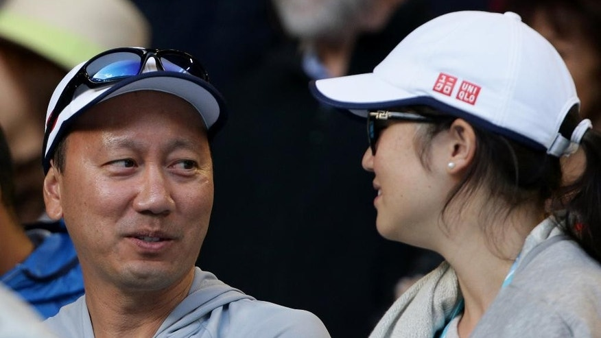 Michael Chang, left, coach of Japan's Kei Nishikori, smiles during his fourth round win  over David Ferrer of Spain at the Australian Open tennis championship in Melbourne, Australia, Monday, Jan. 26, 2015. (AP Photo/Rob Griffith)