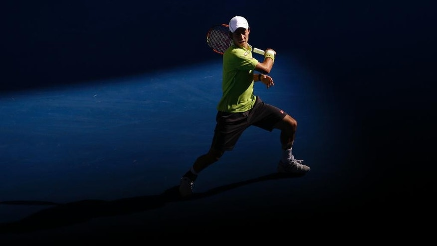 Kei Nishikori of Japan plays a shot to David Ferrer of Spain during their fourth round match at the Australian Open tennis championship in Melbourne, Australia, Monday, Jan. 26, 2015. (AP Photo/Bernat Armangue)