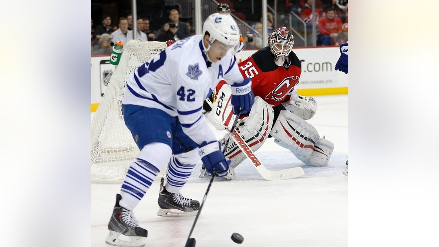 New Jersey Devils goalie Cory Schneider, rear, watches as Toronto Maple Leafs center Tyler Bozak skates with the puck during the first period of an NHL hockey game, Wednesday, Jan. 28, 2015, in Newark, N.J. (AP Photo/Julio Cortez)