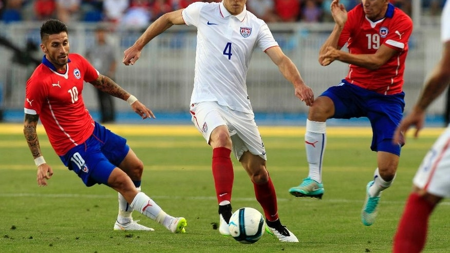 U.S. player Michael Bradley, center, controls the ball under pressure from Chile's Marco Medel, left, and Diego Valdes during their friendly soccer match in Rancagua, Chile, Wednesday, Jan. 28, 2015. (AP Photo/Luis Hidalgo)