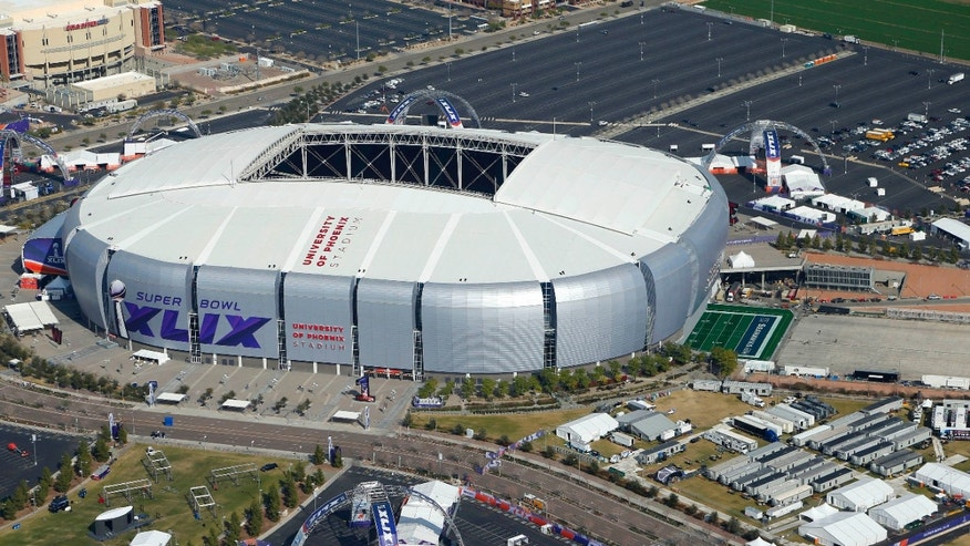 Jan. 28, 2015: In this aerial photo, the playing field for the NFL Super Bowl XLIX football game is rolled into the University of Phoenix Stadium.