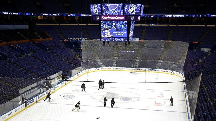 Members of the St. Louis Blues practice as an image of Blues goaltender Martin Brodeur is displayed on a video scoreboard Thursday, Jan. 29, 2015, in St. Louis. Brodeur announced his retirement from the NHL during a news conference on Thursday. He will remain with the Blues as a senior adviser to general manager Doug Armstrong. (AP Photo/Jeff Roberson)