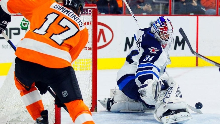 Philadelphia Flyers' Wayne Simmonds (17) left, makes a wrist shot blocked by Winnipeg Jets goalie Michael Hutchinson (34) right in the second  period of an NHL hockey game, Thursday, Jan. 29, 2015, in Philadelphia. (AP Photo/Tom Mihalek)