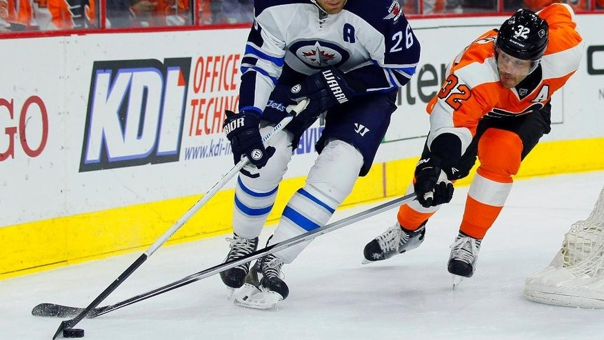 Winnipeg Jets' Blake Wheeler (26), left, brings the puck around the back of the net followed by Philadelphia Flyers' Mark Streit (32) in the first period of an NHL hockey game, Thursday, Jan. 29, 2015, in Philadelphia. (AP Photo/Tom Mihalek)
