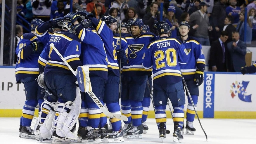 Teammates surround St. Louis Blues goalie Brian Elliott (1) after the Blues' 5-4 victory over the Nashville Predators in an NHL hockey game Thursday, Jan. 29, 2015, in St. Louis. The Blues won 5-4 in a shootout. (AP Photo/Jeff Roberson)