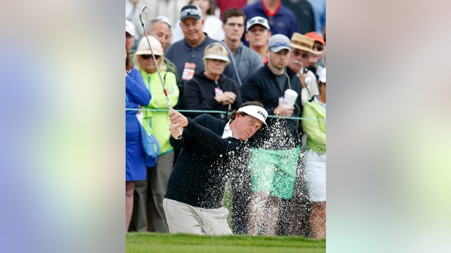 Phil Mickelson hits out of the bunker on the 11th hole during the first round of the Phoenix Open golf tournament, Thursday, Jan. 29, 2015, in Scottsdale, Ariz. (AP Photo/Rick Scuteri)
