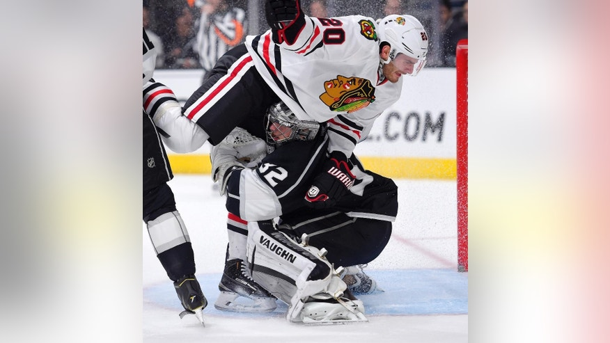 Chicago Blackhawks left wing Brandon Saad, top, collides with Los Angeles Kings goalie Jonathan Quick during the first period of an NHL hockey game, Wednesday, Jan. 28, 2015, in Los Angeles. (AP Photo/Mark J. Terrill)
