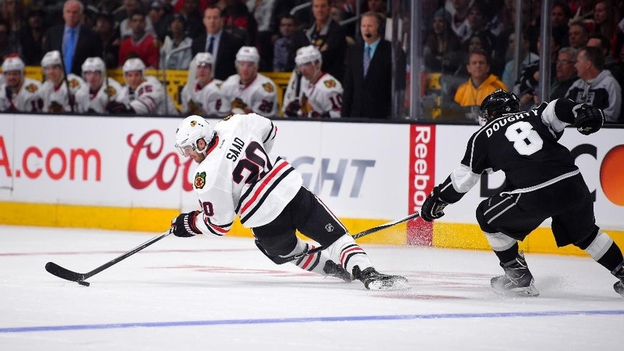 Chicago Blackhawks left wing Brandon Saad, left, is pulled down by Los Angeles Kings defenseman Drew Doughty during the first period of an NHL hockey game, Wednesday, Jan. 28, 2015, in Los Angeles.   (AP Photo/Mark J. Terrill)
