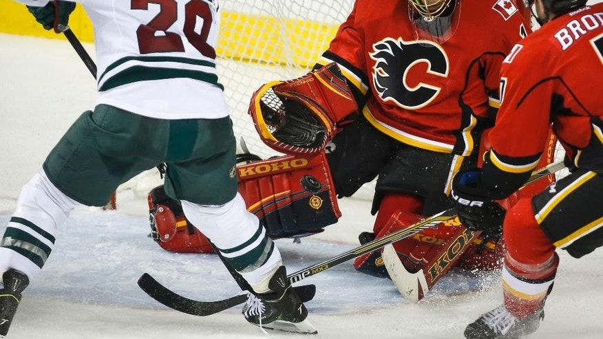 Minnesota Wild Jason Pominville, left, has his shot blocked by Calgary Flames goalie Jonas Hiller, from Switzerland, during third period NHL hockey action in Calgary, Thursday, Jan. 29, 2015. (AP Photo/The Canadian Press, Jeff McIntosh)