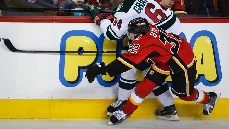 Minnesota Wild Mikael Granlund, left, from Finland, gets checked by Calgary Flames Paul Byron during second period NHL hockey action in Calgary, Thursday, Jan. 29, 2015. (AP Photo/The Canadian Press, Jeff McIntosh)