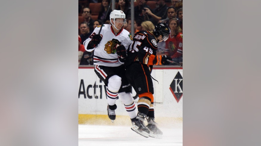 Chicago Blackhawks center Joakim Nordstrom, left, of Sweden gets a hip check from Anaheim Ducks defenseman Sami Vatanen (45), of Finland during the first period of an NHL hockey game in Anaheim, Calif., Friday, Jan. 30, 2015. (AP Photo/Alex Gallardo)
