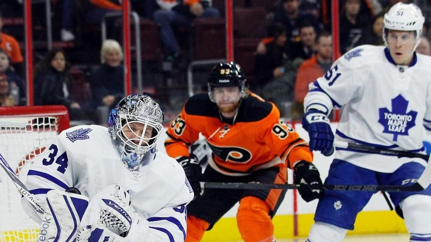 Toronto Maple Leafs goalie James Reimer, left, holds on to the puck as Philadelphia Flyers' Jakub Voracek, center, and Jake Gardiner, right, look on in the second period of an NHL hockey game, Saturday, Jan. 31, 2015, in Philadelphia. (AP Photo/Tom Mihalek)