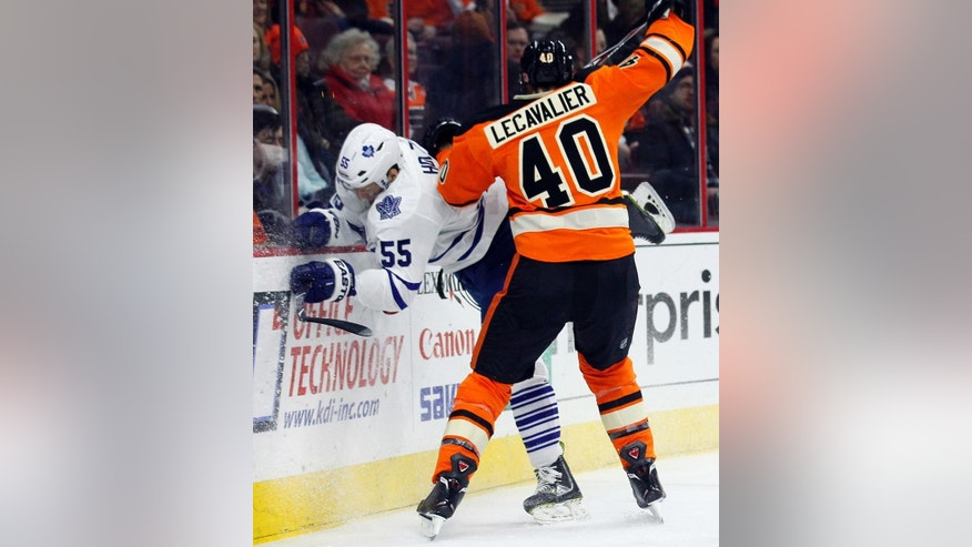 Toronto Maple Leafs' Korbinian Holzer, left, gets checked into the boards by Philadelphia Flyers' Vincent Lecavalier, right, in the second period of an NHL hockey game, Saturday, Jan. 31, 2015, in Philadelphia. (AP Photo/Tom Mihalek)