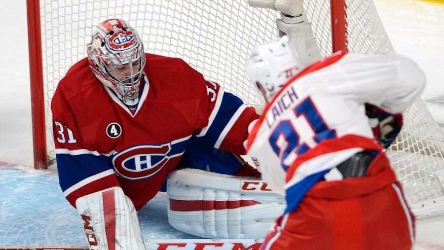Montreal Canadiens goalie Carey Price (31) makes the save against Washington Capitals center Brooks Laich (21)during the first period of an NHL hockey game Saturday, Jan. 31, 2015,  in Montreal. (AP Photo/The Canadian Press, Ryan Remiorz)