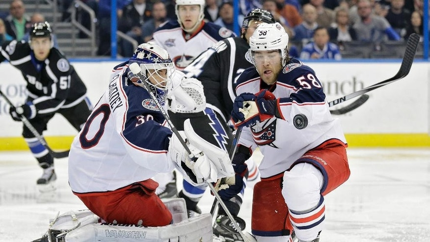 Columbus Blue Jackets goalie Curtis McElhinney (30) makes a blocker save on a shot by the Tampa Bay Lightning during the second period of an NHL hockey game Saturday, Jan. 31, 2015, in Tampa, Fla. Defending is David Savard (58). (AP Photo/Chris O'Meara)
