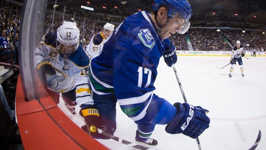Vancouver Canucks' Radim Vrbata, right, of the Czech Republic, and Buffalo Sabres' Brian Gionta (12) battle for the puck along the boards during the first period of an NHL hockey game Friday, Jan. 30, 2015, in Vancouver, British Columbia. (AP Photo/The Canadian Press, Darryl Dyck)