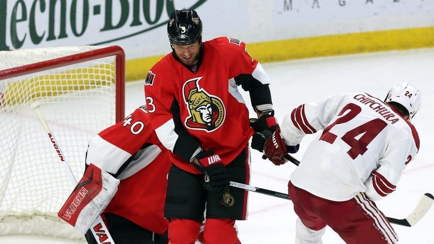 Ottawa Senators' Marc Methot (3) holds the stick of Arizona Coyotes' Kyle Chipchura (24) as Senators goaltender Robin Lehner (40) makes a save during the second period of an NHL hockey game in Ottawa, Ontario, Saturday, Jan. 31, 2015. (AP Photo/The Canadian Press, Fred Chartrand)