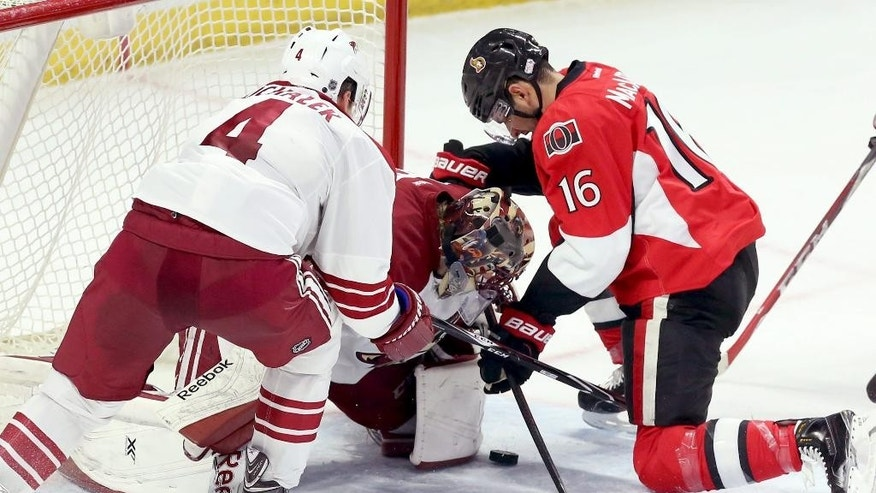 Ottawa Senators' Clarke MacArthur (16) fights for the puck with Arizona Coyotes' goaltender Mike Smith (41) and Zbynek Michalek (4) reacts during the first period of an NHL hockey game in Ottawa, Ontario, Saturday, Jan. 31, 2015. (AP Photo/The Canadian Press, Fred Chartrand)