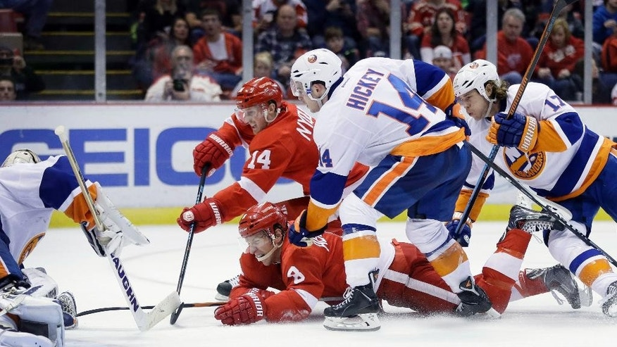 Detroit Red Wings center Gustav Nyquist (14), of Sweden, shoots towards New York Islanders goalie Chad Johnson, left, as Detroit Red Wings left wing Justin Abdelkader (8) falls in front of Islanders defenseman Thomas Hickey (14) and left wing Matt Martin (17), during the second period of an NHL hockey game, Saturday, Jan. 31, 2015 in Detroit. (AP Photo/Carlos Osorio)