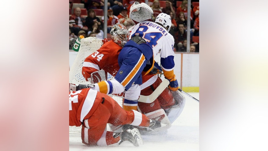 New York Islanders center Mikhail Grabovski (84) crashes into Detroit Red Wings goalie Petr Mrazek (34), of the Czech Republic, during the first period of an NHL hockey game, Saturday, Jan. 31, 2015, in Detroit. (AP Photo/Carlos Osorio)