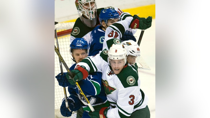 Minnesota Wild's Charlie Coyle (3) and Jared Spurgeon (46) try to clear Vancouver Canucks Daniel Sedin (22) and Alex Burrows (14) from in front of Wild goalie Devan Dubnyk (40) during the third period of NHL action in Vancouver, British Columbia, Sunday, Feb. 1, 2015.  (AP Photo/The Canadian Press, Jonathan Hayward)