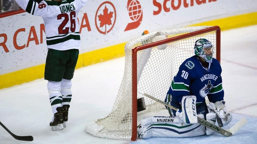 Minnesota Wild left winger Thomas Vanek (26) celebrates teammate Kyle Brodziak's goal past Vancouver Canucks goalie Ryan Miller (30) during the second period of NHL action in Vancouver, British Columbia, Canada, Sunday, Feb. 1, 2015. (AP Photo/The Canadian Press, Jonathan Hayward)
