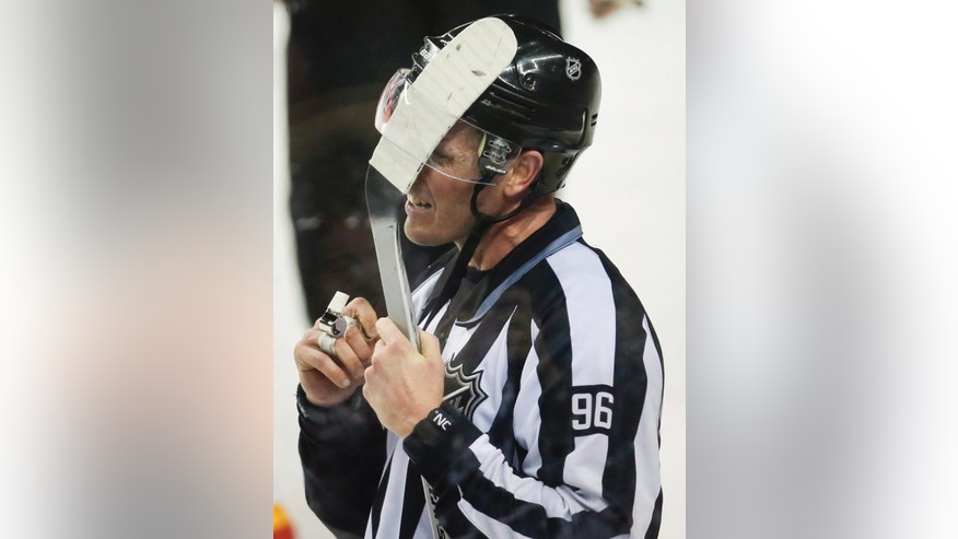 Linesman David Brisebois has a stick stuck in his helmet as the Edmonton Oilers play the Calgary Flames during the third period of an NHL hockey game Saturday, Jan. 31, 2015, in Calgary, Alberta. (AP Photo/The Canadian Press, Jeff McIntosh)