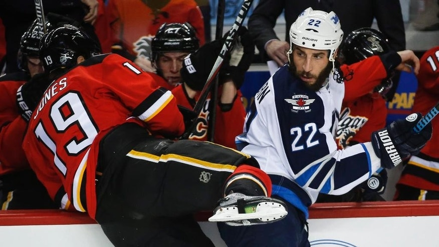 Winnipeg Jets Chris Thorburn, right, checks Calgary Flames David Jones during first period of an NHL hockey game in Calgary, Alberta, Monday, Feb. 2, 2015. (AP Photo/The Canadian Press, Jeff McIntosh)