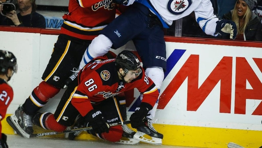 Winnipeg Jets Adam Lowry, right, gets checked by Calgary Flames Deryk Engelland, left, and Josh Jooris during the second period of an NHL hockey game in Calgary, Alberta, Monday, Feb. 2, 2015. (AP Photo/The Canadian Press, Jeff McIntosh)