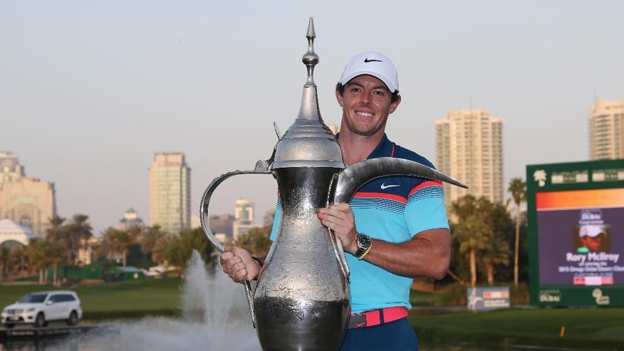 Rory McIlroy of Northern Ireland holds the trophy after he wins the final round of the Dubai Desert Classic golf tournament in United Arab Emirates, Sunday, Feb. 1, 2015. (AP Photo/Kamran Jebreili)