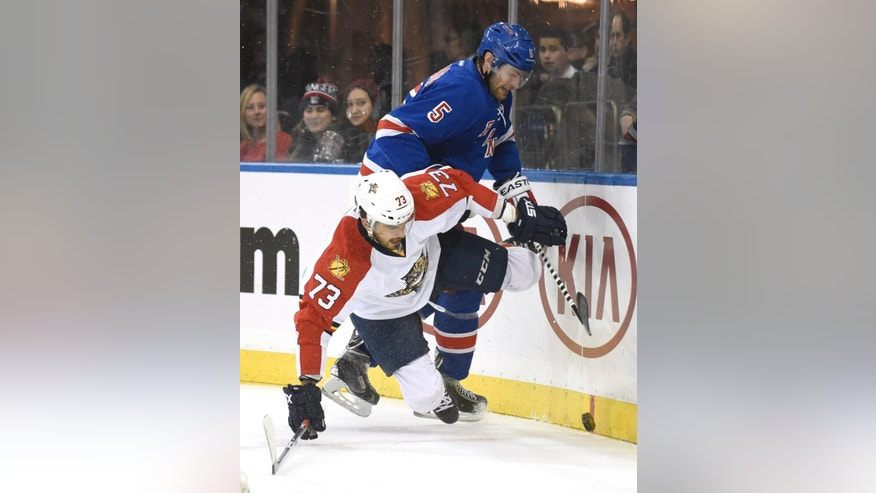 New York Rangers' Dan Girardi (5) checks Florida Panthers' Brandon Pirri during the first period of an NHL hockey game Monday, Feb. 2, 2015, at Madison Square Garden in New York. (AP Photo/Bill Kostroun)