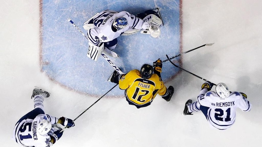 Nashville Predators forward Mike Fisher (12) scores a goal against Toronto Maple Leafs goalie Jonathan Bernier (45) in the third period of an NHL hockey game Tuesday, Feb. 3, 2015, in Nashville, Tenn. Also defending for the Maple Leafs are Jake Gardiner (51) and James van Riemsdyk (21). (AP Photo/Mark Humphrey)