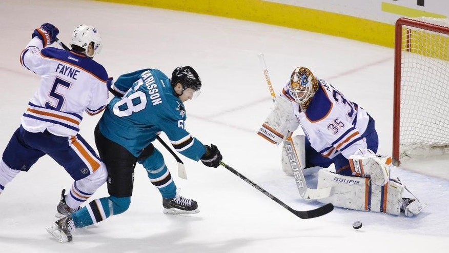 San Jose Sharks right wing Melker Karlsson (68) makes a shot against Edmonton Oilers goalie Viktor Fasth (35) as Oilers defenseman Mark Fayne (5) tries to  defend during the first period of their NHL hockey game Monday, Feb. 2, 2015, in San Jose, Calif. (AP Photo/Eric Risberg)