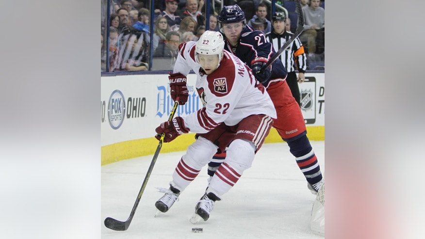 Arizona Coyotes' Brandon McMillan, front, controls the puck as Columbus Blue Jackets' Ryan Murray defends during the first period of an NHL hockey game Tuesday, Feb. 3, 2015, in Columbus, Ohio. (AP Photo/Jay LaPrete)