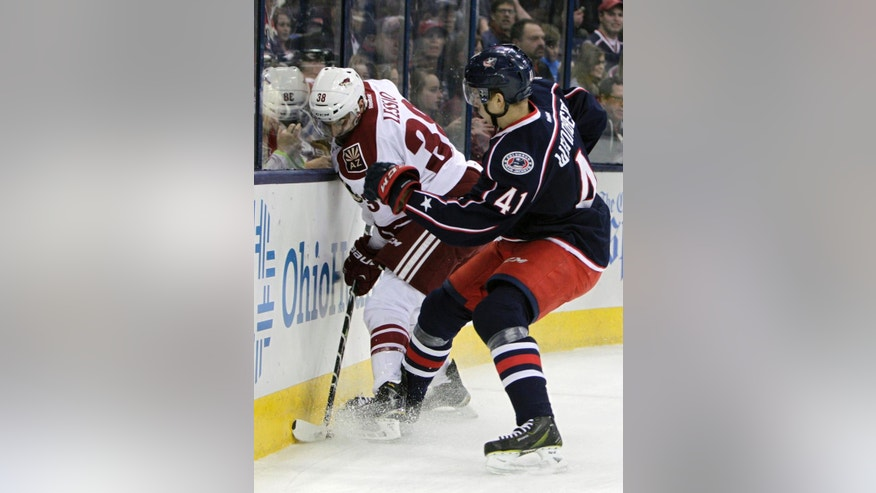 Columbus Blue Jackets' Alexander Wennberg, left, of Sweden, checks Arizona Coyotes' Lucas Lessio during the first period of an NHL hockey game Tuesday, Feb. 3, 2015, in Columbus, Ohio. (AP Photo/Jay LaPrete)